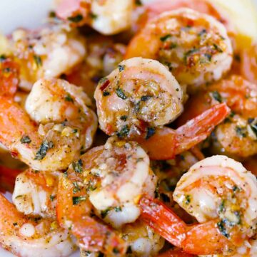 Square photo of sauteed shrimp with garlic and herbs.