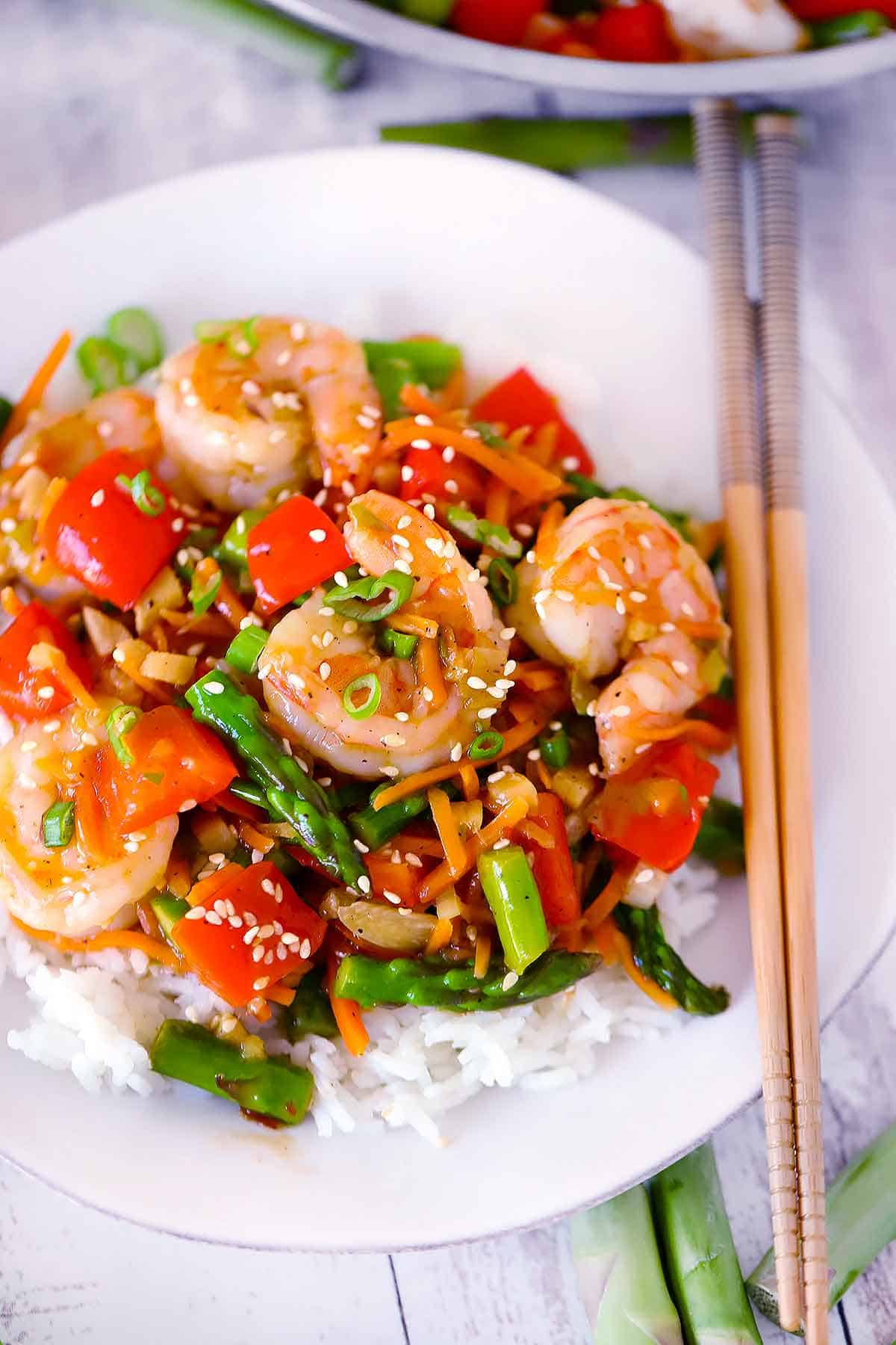 Close up photo of shrimp and vegetable stir fry on a white plate with chopsticks on the side.