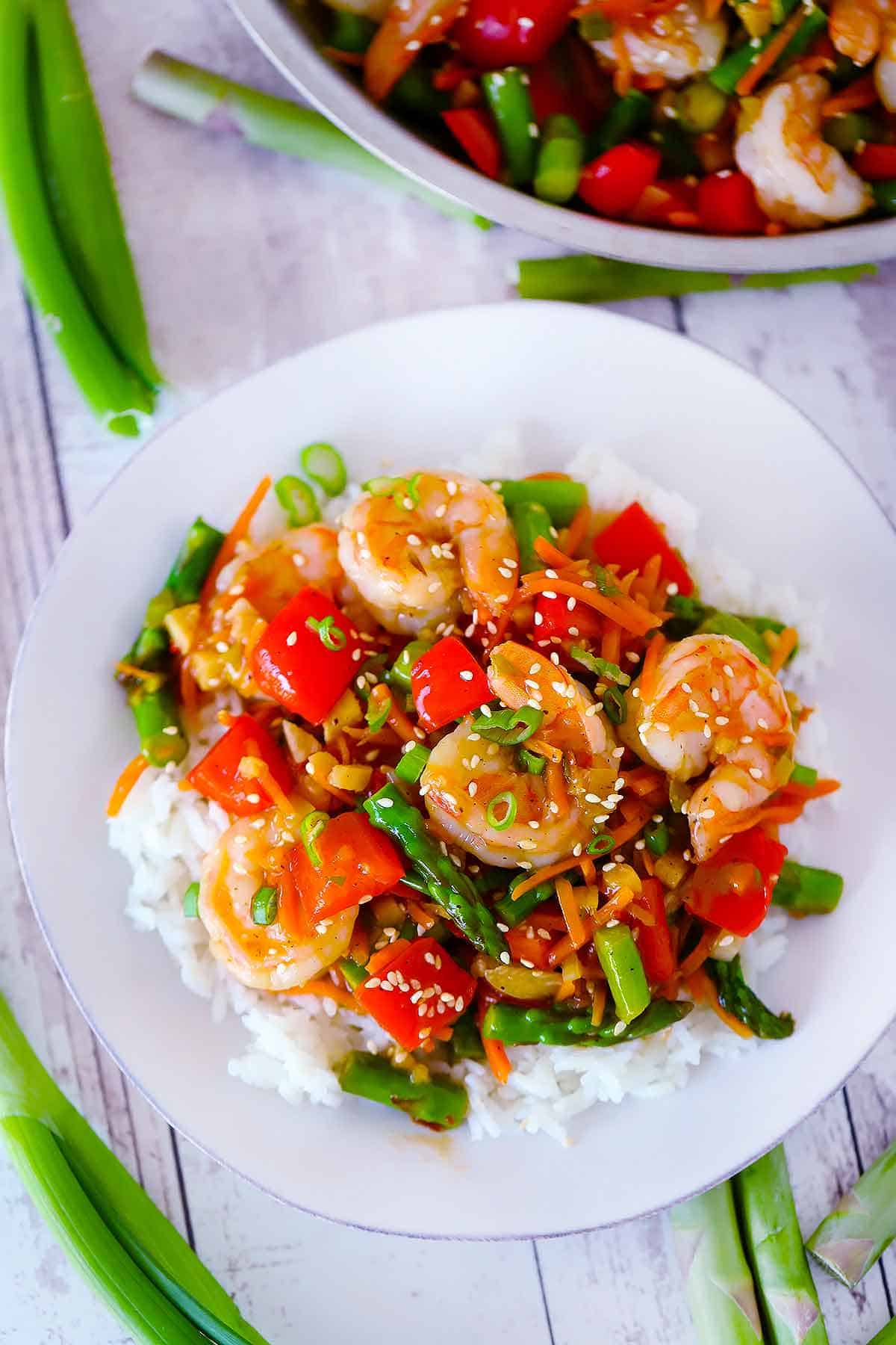 An overhead photo of a white plate with rice and shrimp stir fry on it.