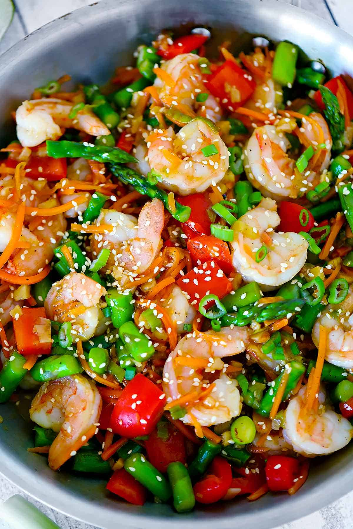 Overhead photo of a skillet with shrimp stir fry, peppers, and asparagus in it garnished with sesame seeds.