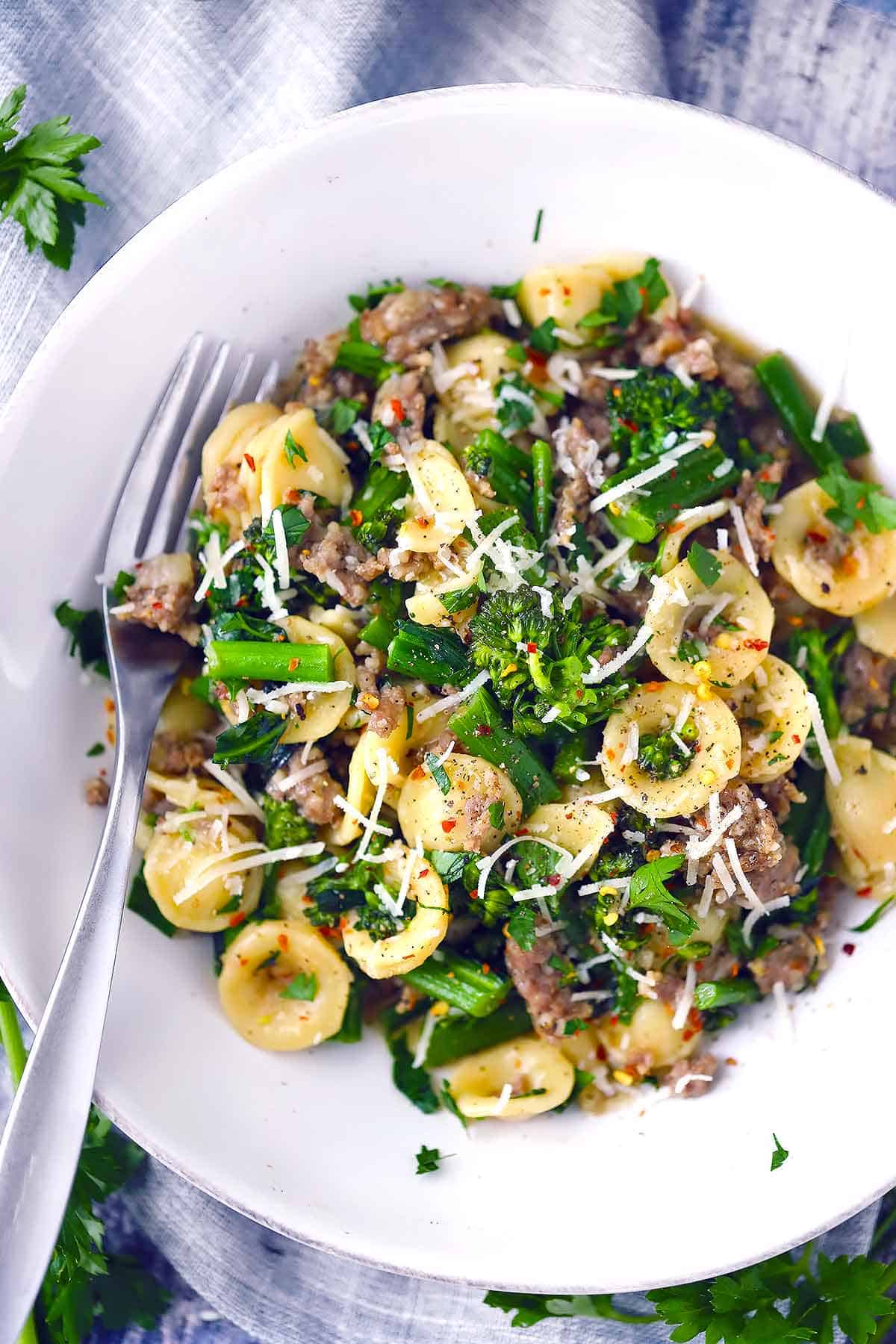 Overhead photo of a white bowl filled with orecchiette, broccolini, and sausage garnished with parmesan with a fork.