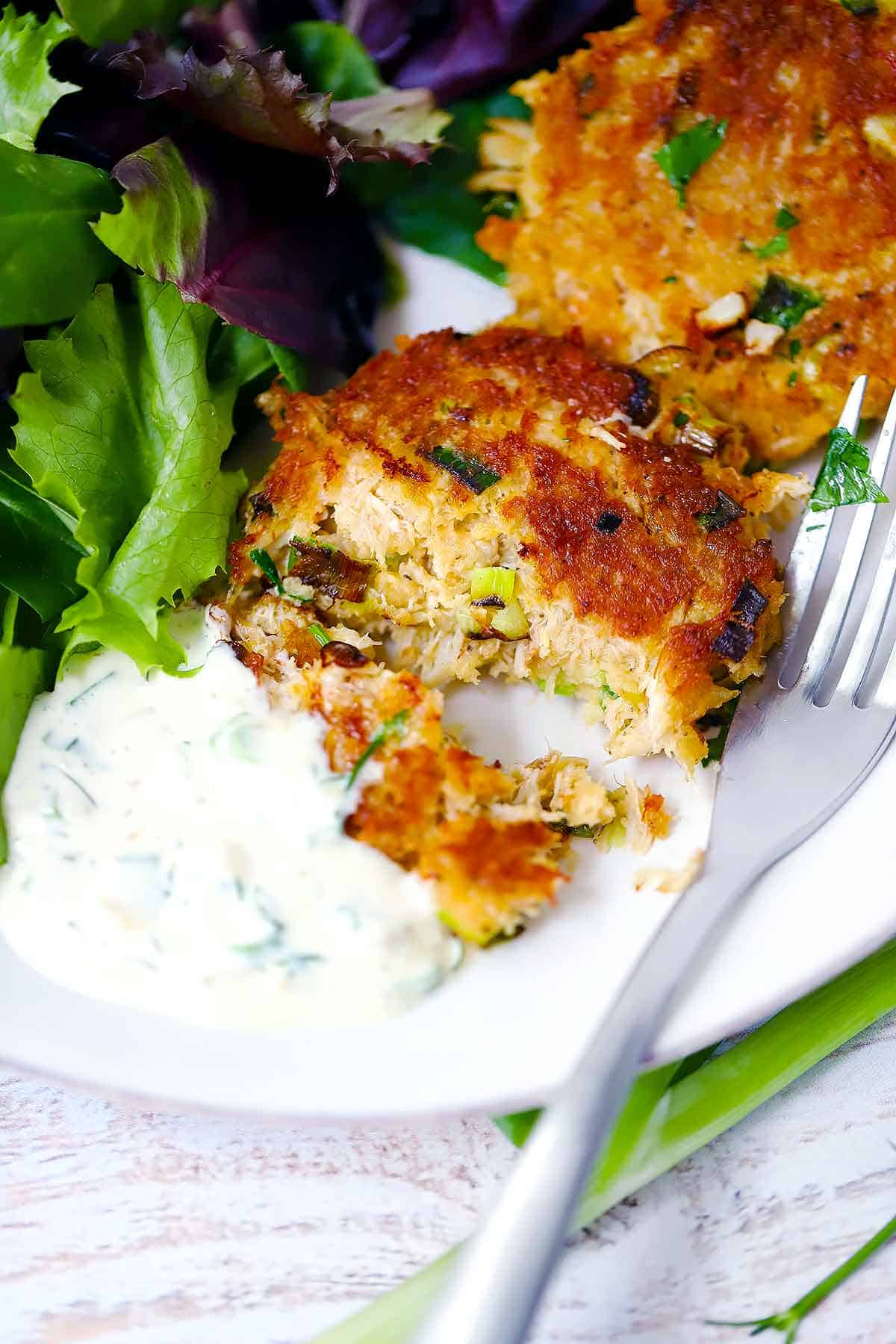 A crab cake cut in half with a fork on a white plate served with tartar sauce and salad on the side.