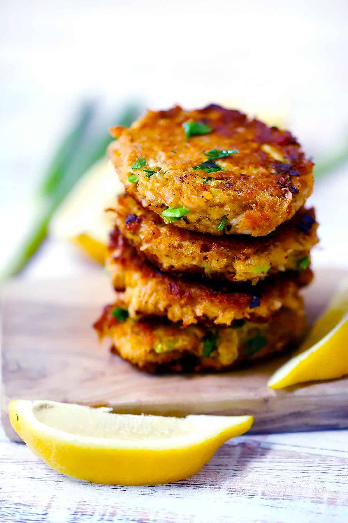 A stack of crab cake patties with fresh lemon wedges around it.