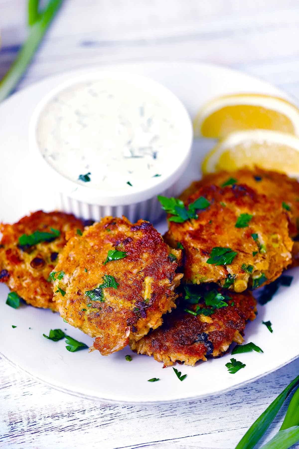 Crab cake patties on a white plate with tartar sauce and lemon wedges.