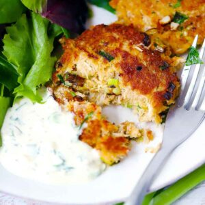 Square photo of a crab cake cut in half with a fork on a white plate.