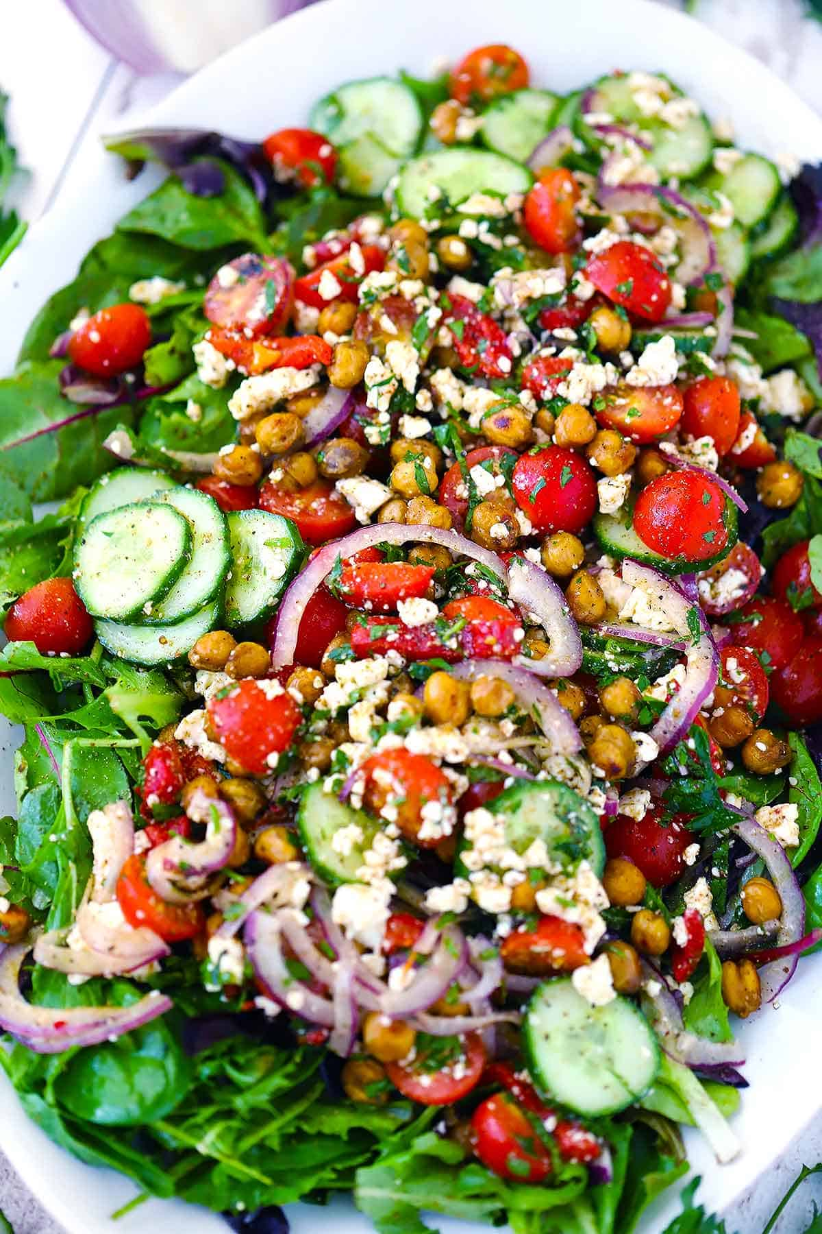 Close up photo of a salad with za'atar roasted chickpeas, cucumbers, tomatoes, onions, feta, and other Mediterranean ingredients.