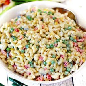 Square photo of macaroni salad in a white bowl.