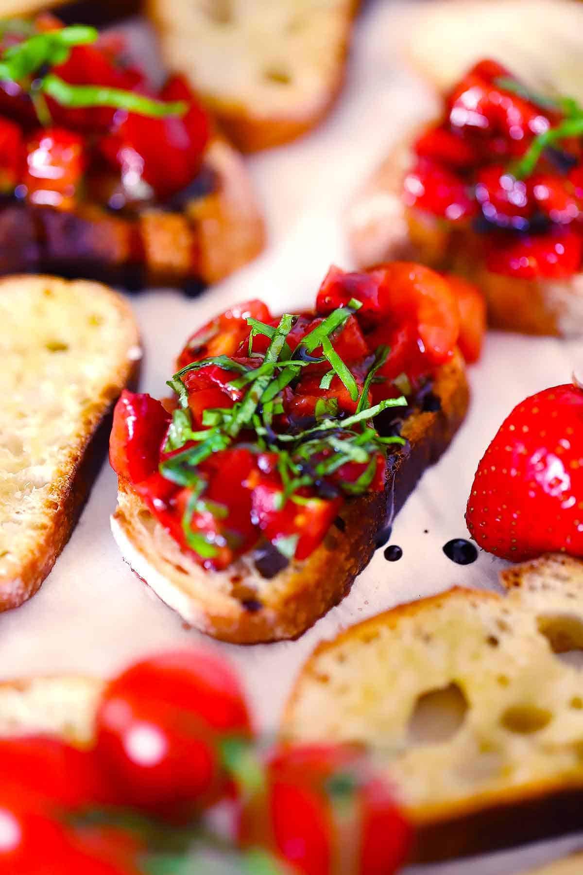 Close up photo of a crostini topped with strawberry bruschetta, balsamic glaze, and fresh basil.