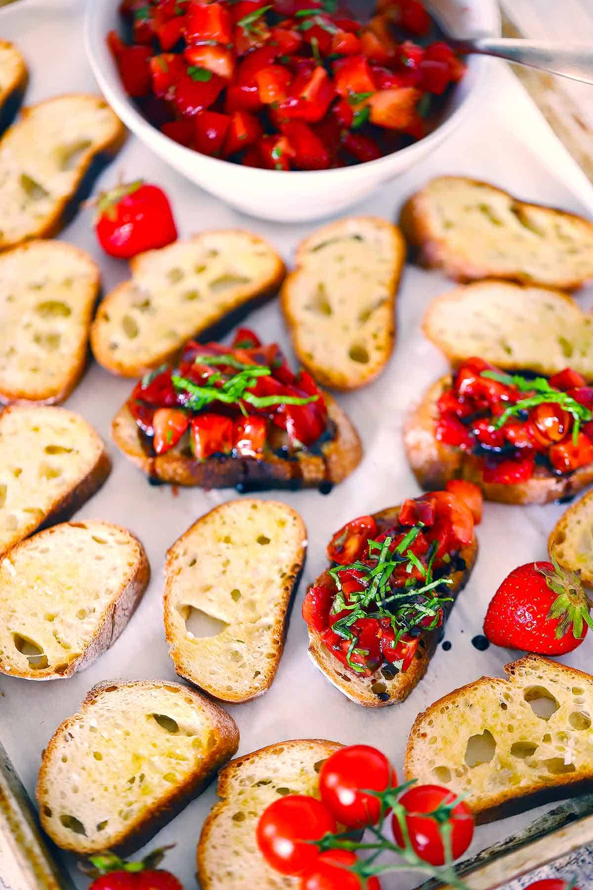 Crostini on a baking sheet with strawberry bruschetta on top of three.