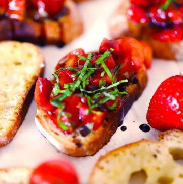 Square photo of strawberry bruschetta on a crostini with fresh basil garnish.