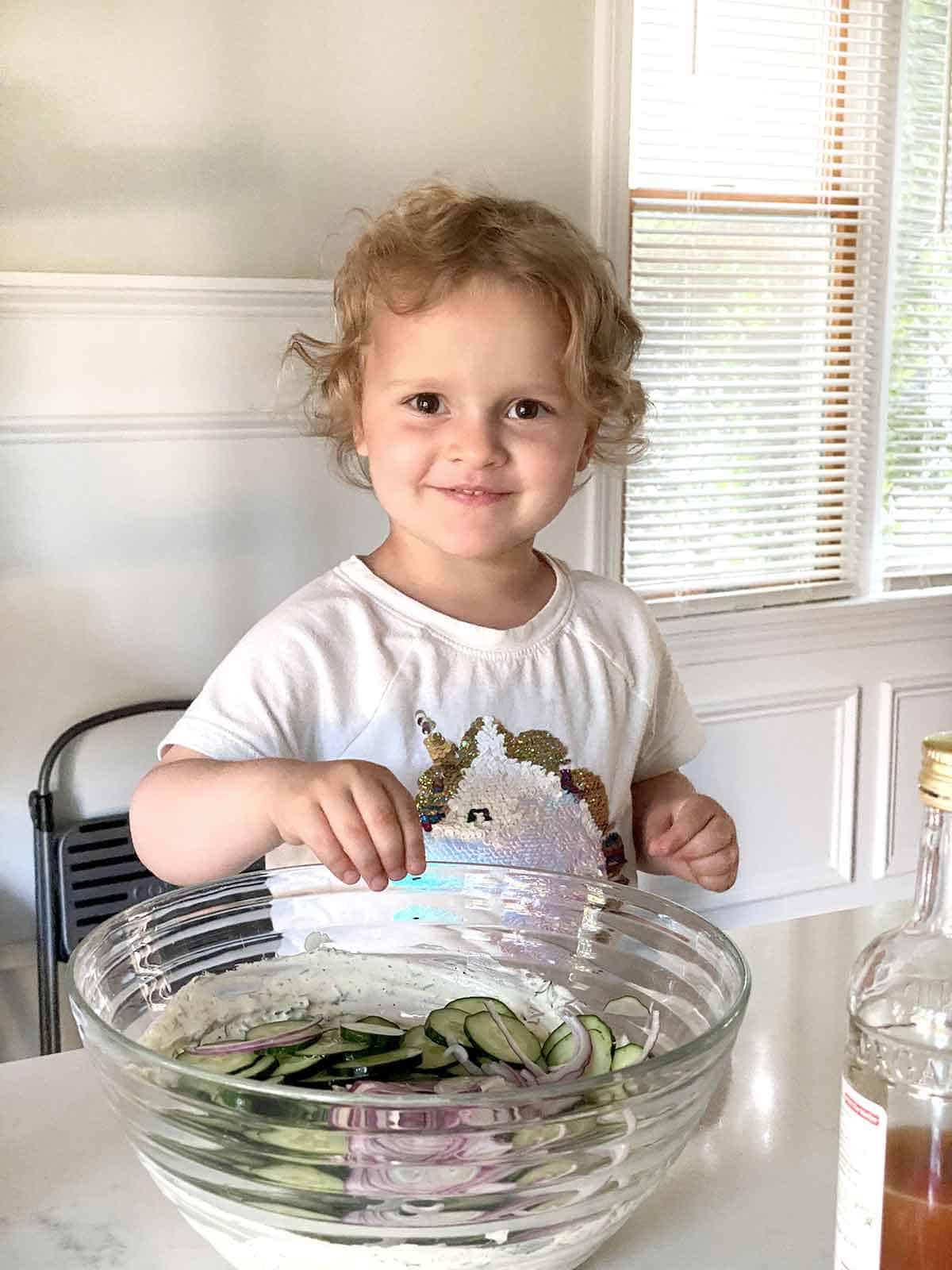 Three year old child helping make salad.