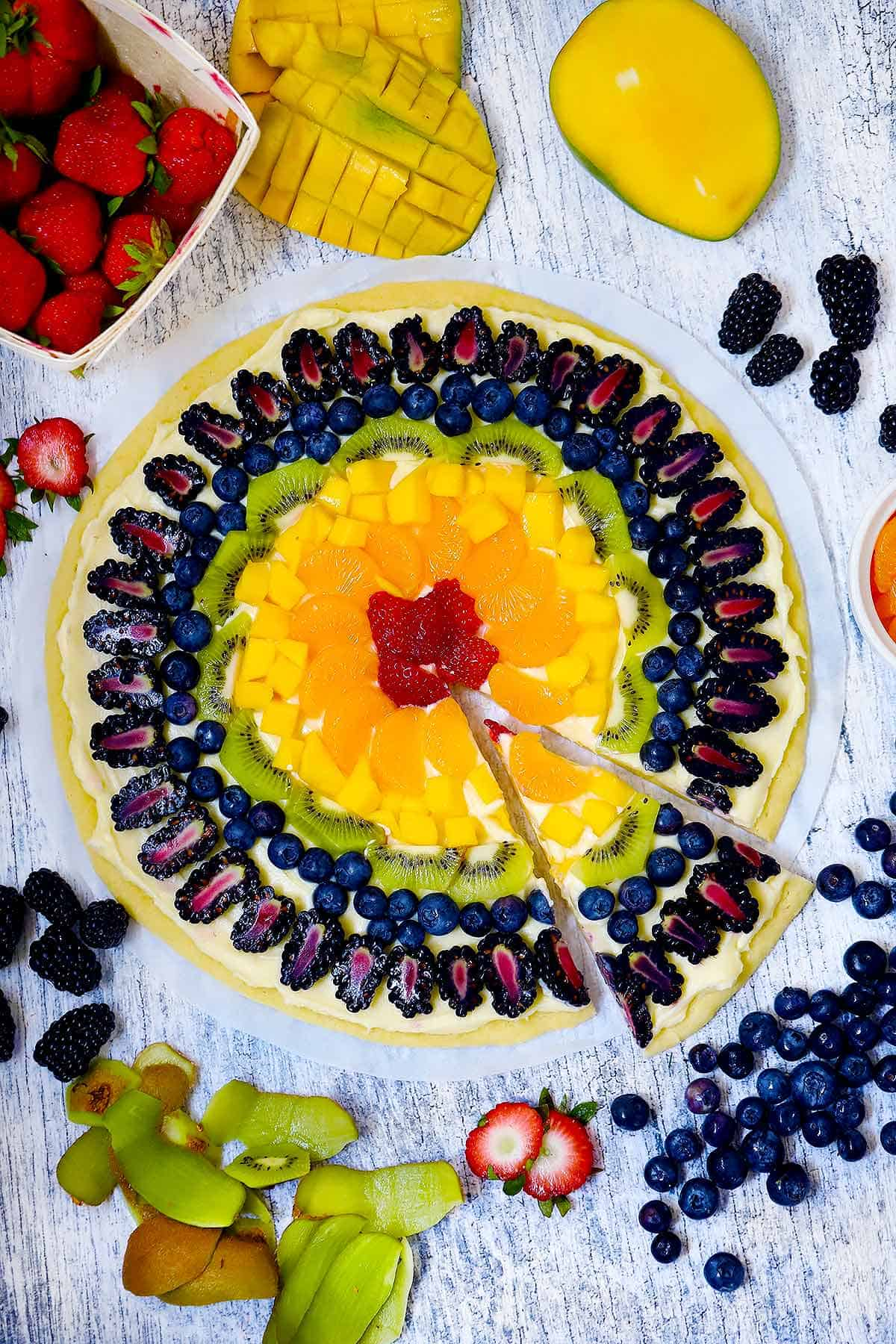 Overhead photo of a fruit pizza with rainbow fruit colors and fruit scattered around it.