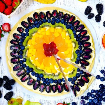 Square photo of rainbow fruit pizza with a slice taken out.