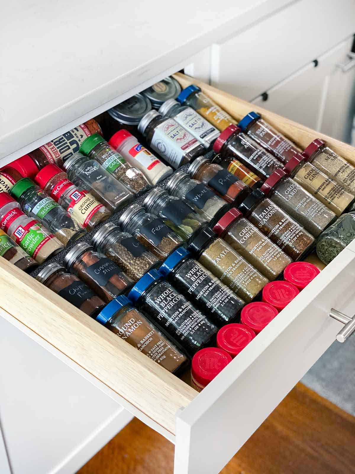 A drawer open with spices inside arranged on a drawer spice rack.