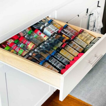 Square photo of a drawer open in the kitchen with spices.