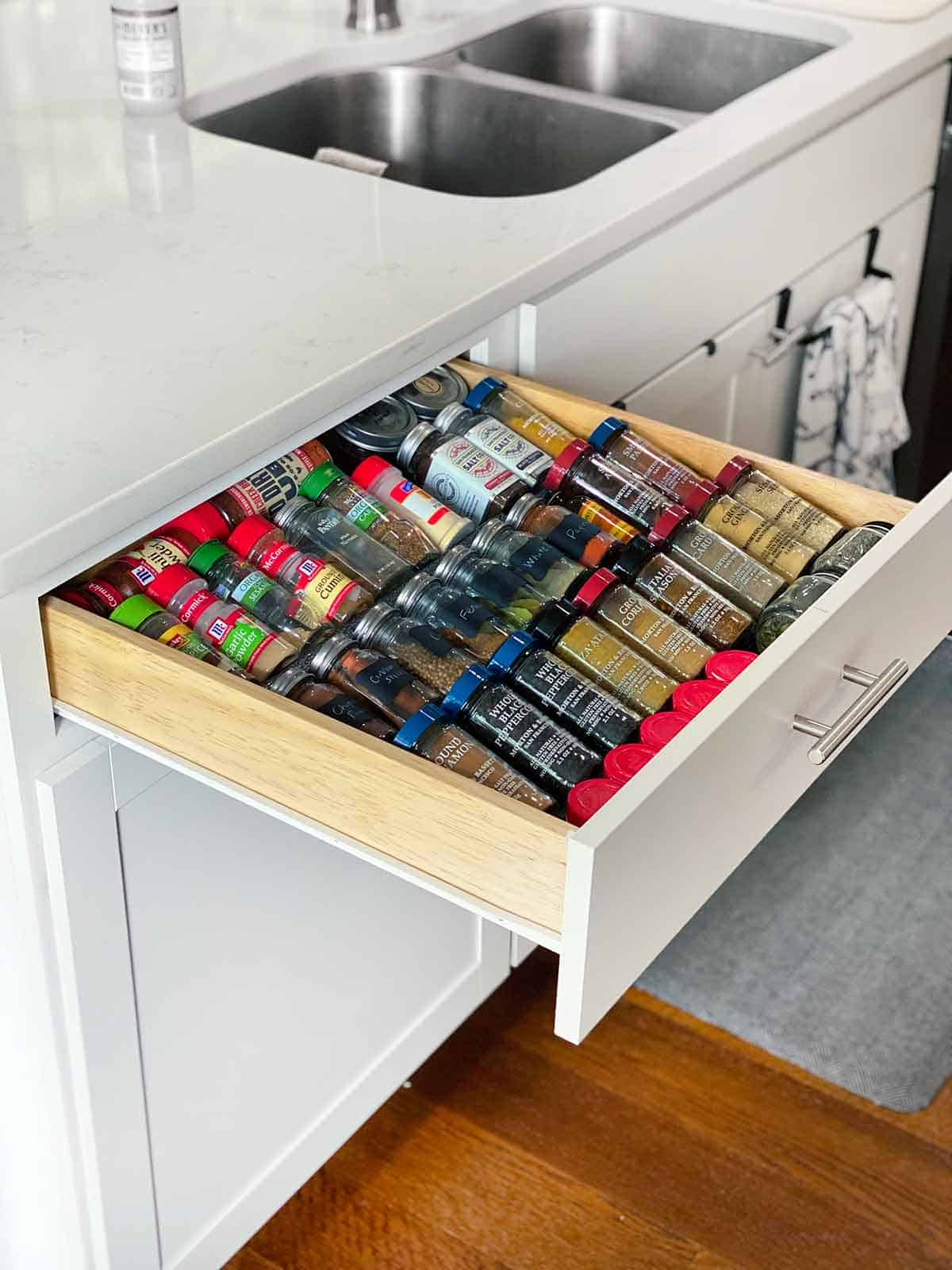 An open kitchen drawer with spices arranged on a rack.