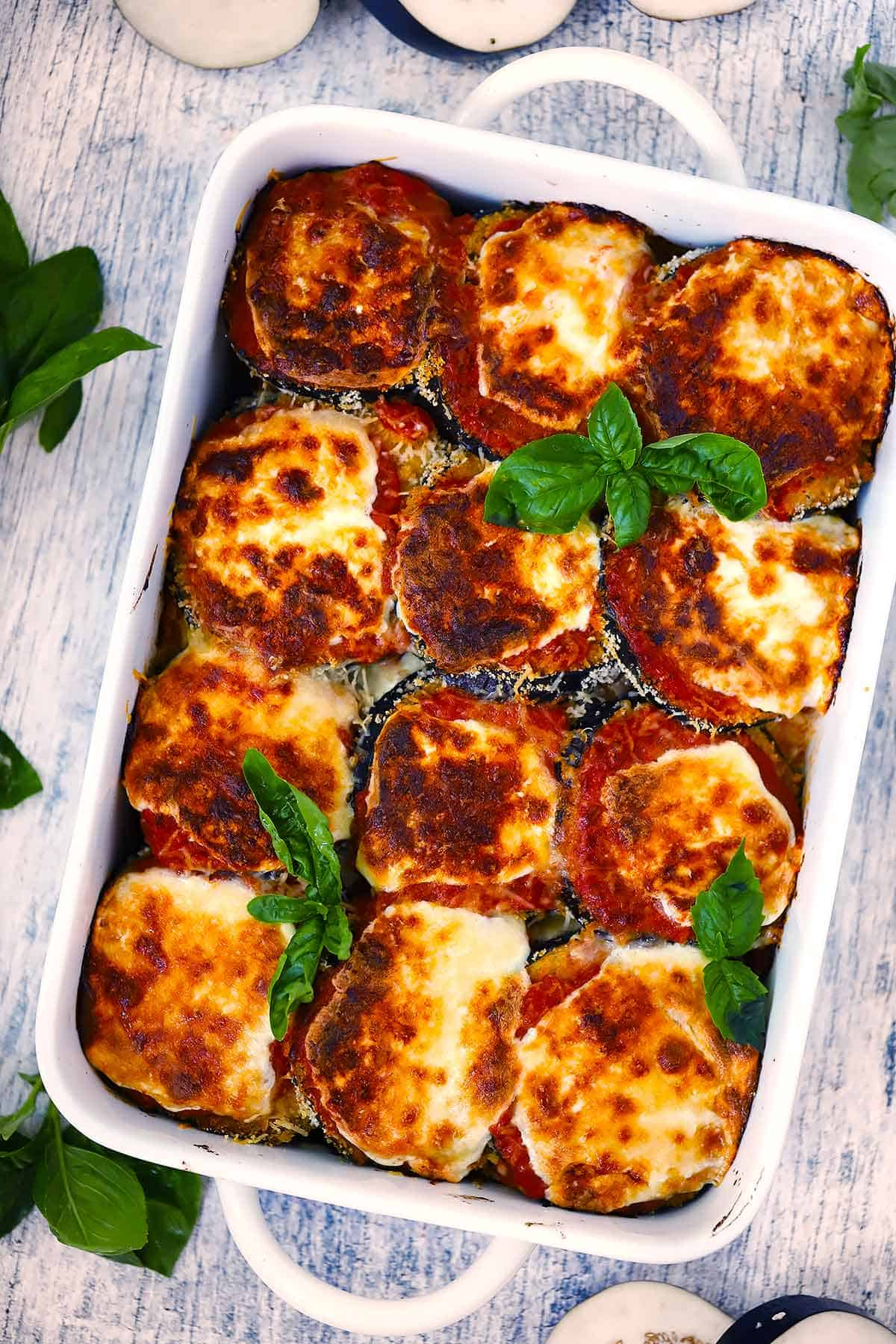 Overhead photo of a white baking dish with eggplant parmesan in it and fresh basil as a garnish.
