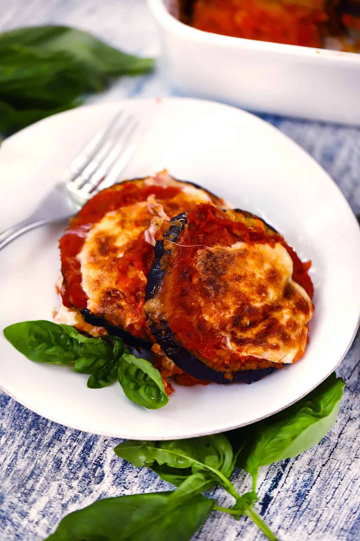 Eggplant parmesan on a white plate with a garnish of fresh basil.
