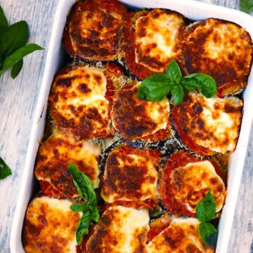 Overhead photo of a white baking dish with eggplant parmesan in it and fresh basil as a garnish with browned crispy cheese on top.