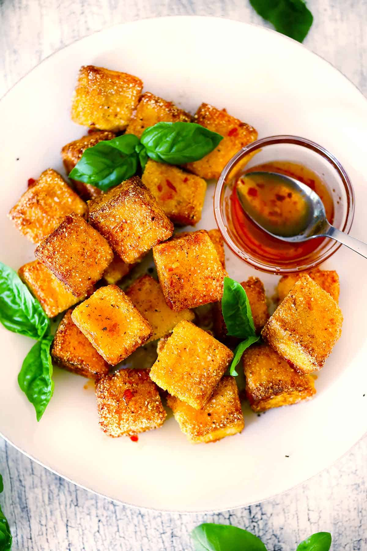 Overhead photo of a plate of fried halloumi garnished with basil with hot spicy honey on the side.