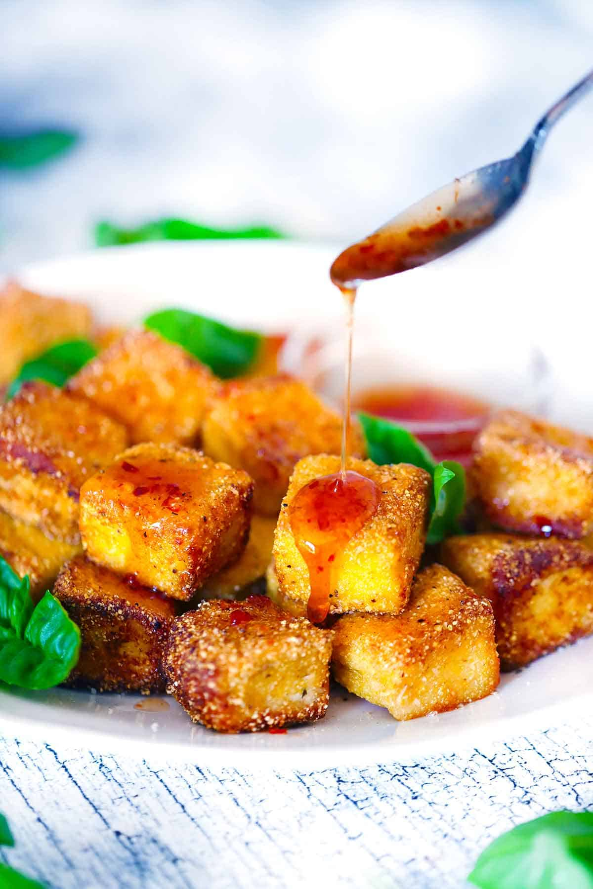 Hot honey being drizzled over a plate of fried halloumi bites.