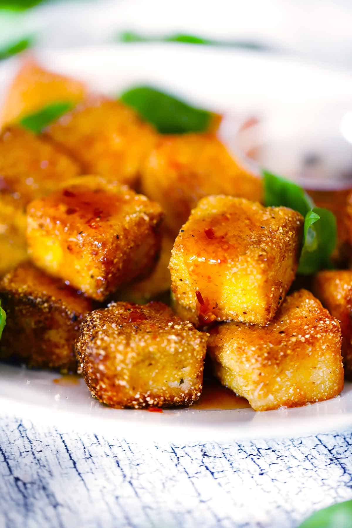 Close up photo of fried halloumi nuggets with hot honey dripping off the side.