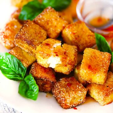 Square photo of fried halloumi bites piled up and drizzled with hot honey.