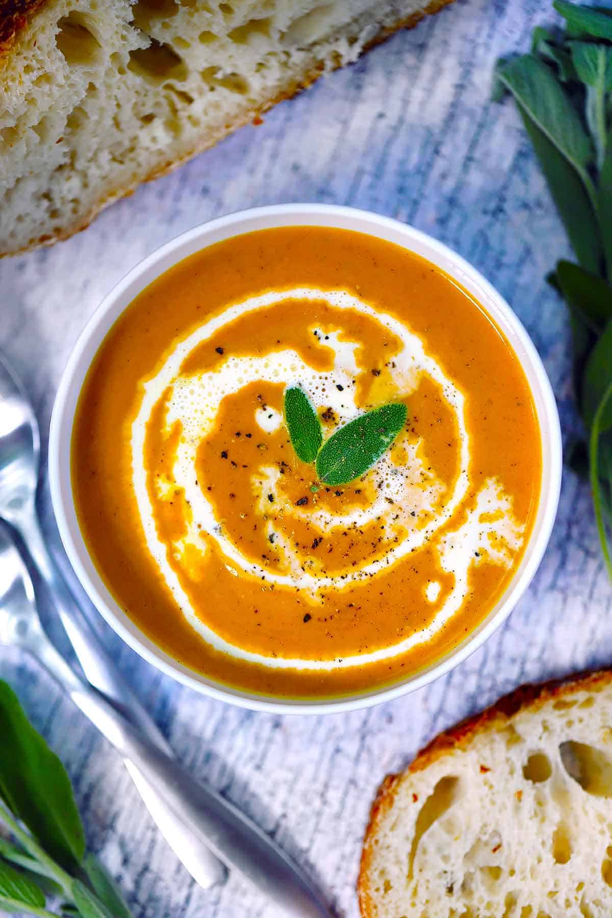 Overhead photo of a bowl of pumpkin soup drizzled with cream and garnished with fresh sage leaves, with bread around it.