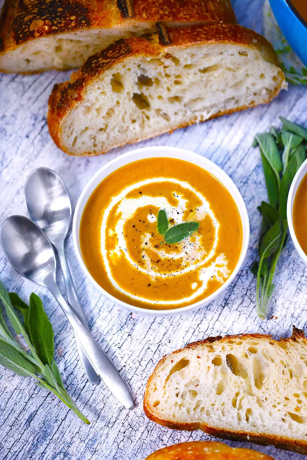 A white bowl with pumpkin soup and sourdough bread and fresh sage scattered around it.