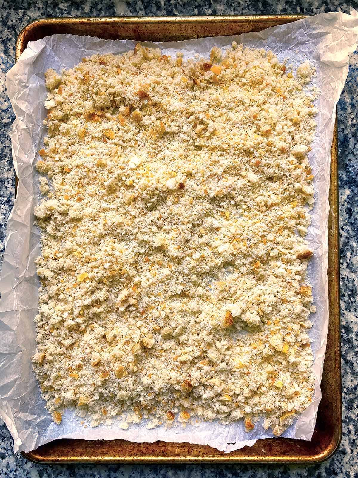 A baking sheet with bread crumbs spread on it to dry them out.