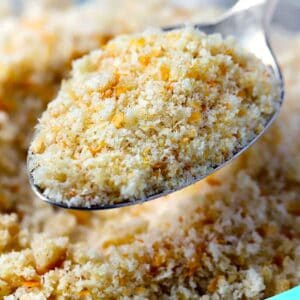 Close up square photo of a spoon scooping homemade bread crumbs.